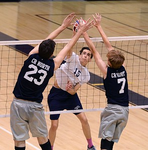 South sophomore Dane Paulson (#15) slams ball at Jason Yakimiv (23) and Logan Fuglestad (7).