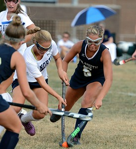 CR North's Anna Lehman (#7) and South's Caroline McGovern (5) lock sticks in rivalry battle.