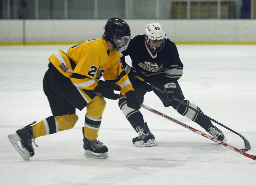 . Collin Kleiser digs puck out in front of Jake Lang.