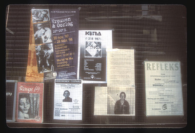 Ads in storefront window, Antwerp, Belgium.
