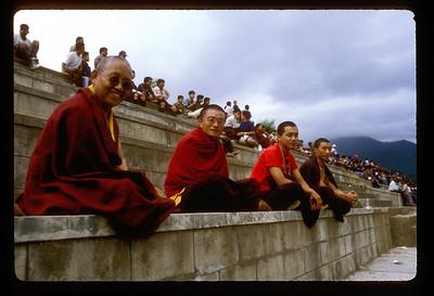 Monks among Thimpu, Bhutan stadium crowd for a football match.
