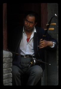 Man plays erhu in his doorway, Dali, China.