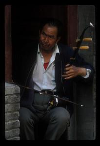 Man plays erhu in his doorway, Dali, China.