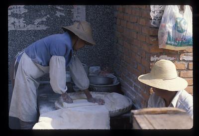 Pounding dough near Dali, China.