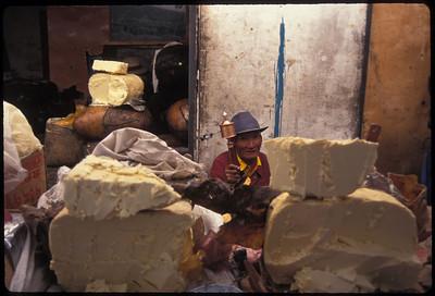 Yak cheese salesman spinning prayer wheel, Barkhor Street around Jokhang Temple, Lhasa, Tibet.