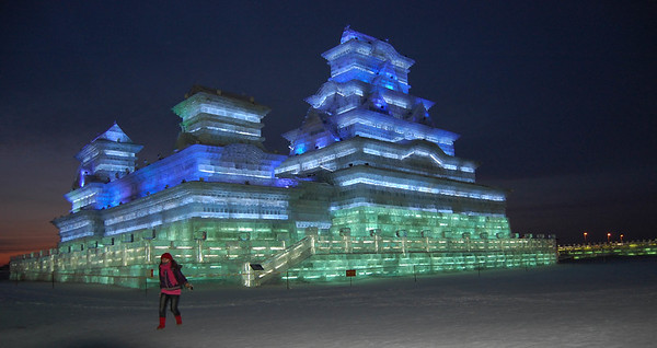 Huge buildings of ice with coloured lights drilled into the blocks