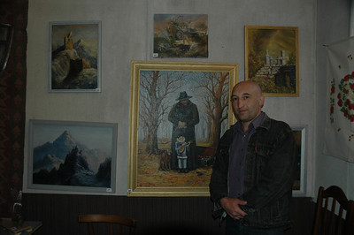 Painter from Vladikavkaz, North Ossetia, Russia, and his work, in Kazbegi town, Republic of Georgia.