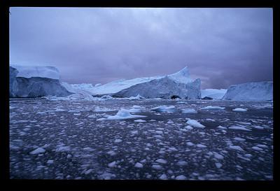 An iceberg breaks apart, Ataa Camp, Greenland.