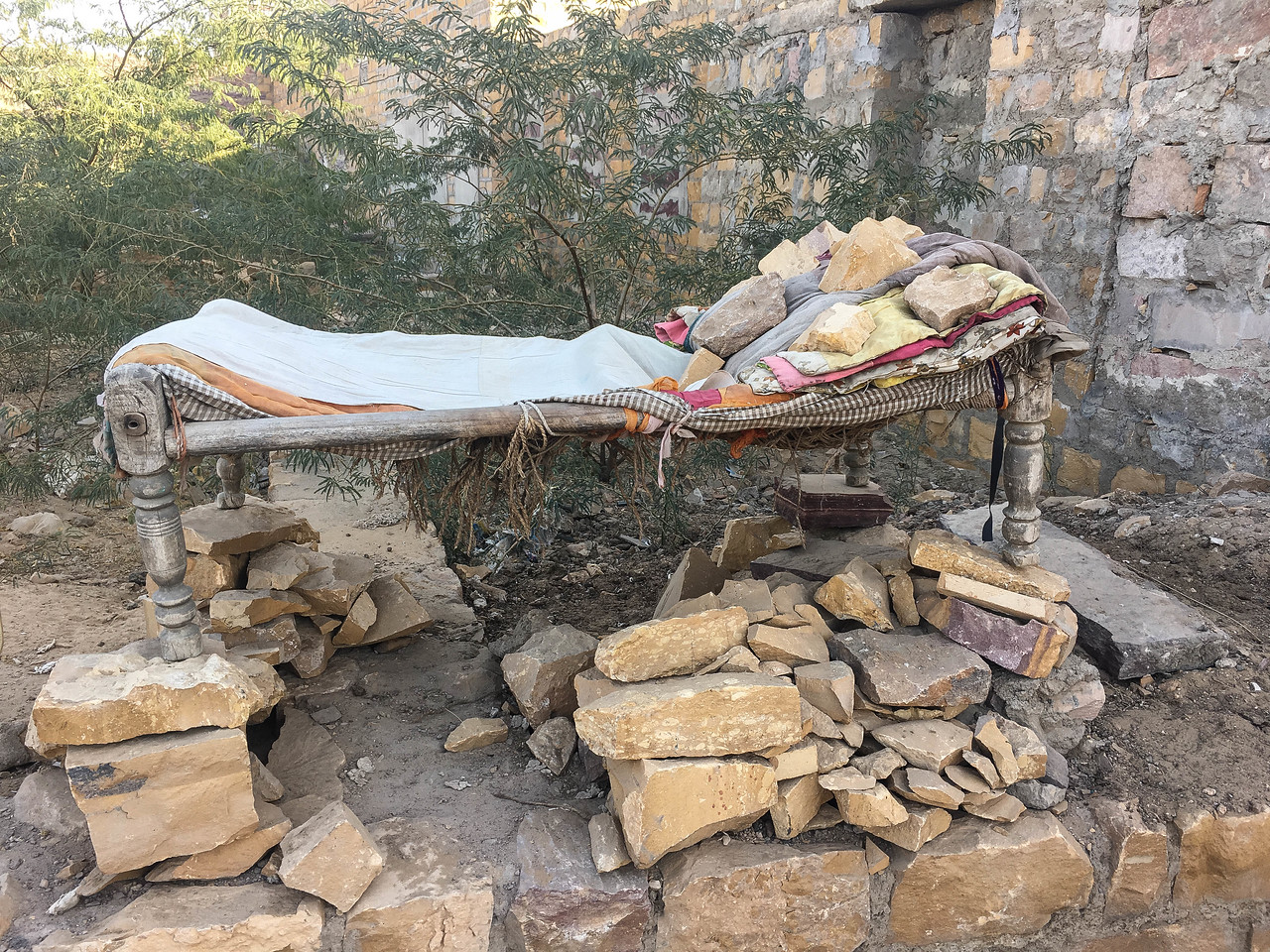 Mr, Natu Dan's bed somehow balanced on these stones. He arrives late every eveniing from hard labour work to warm up in ftont of a fire and sleeps soundly till sunrise. It is a mystery the bed does not topple over. I did not believe the story until I stayed up late one night to check.