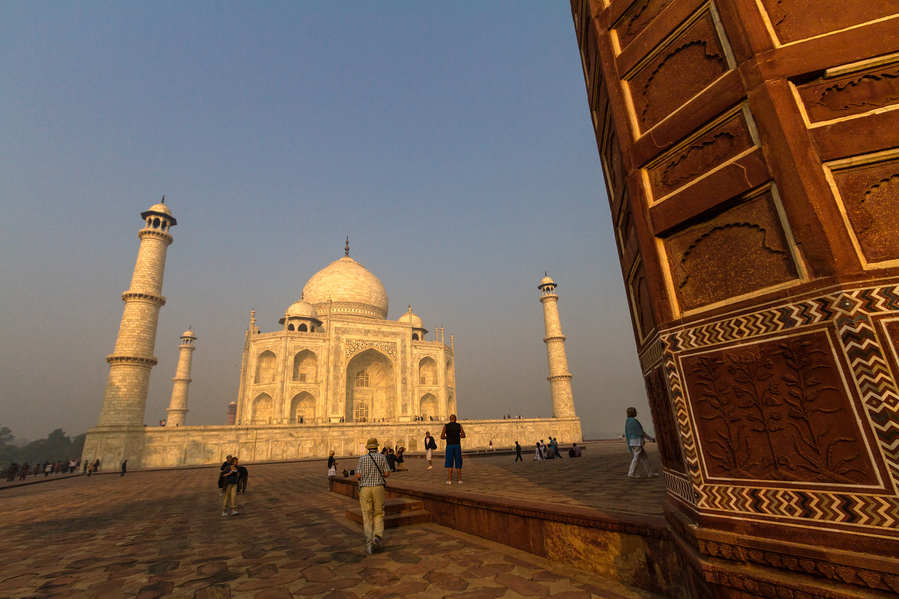 The Taj Mahal is seen in morning light with a red sandstone wall of the Jawab in the foreground. Tourists mill about.