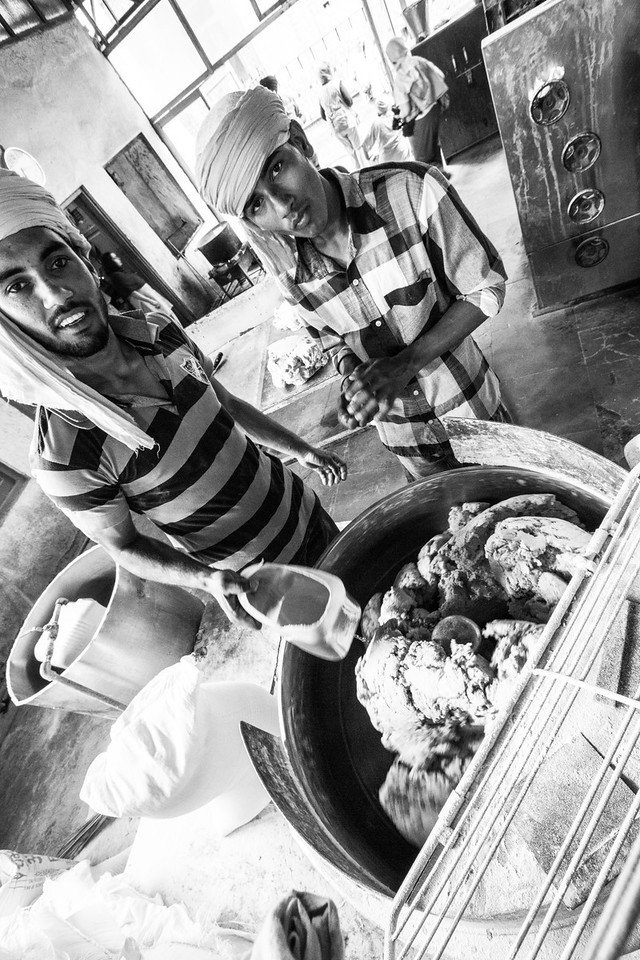 Men preparing food in kitchen - India