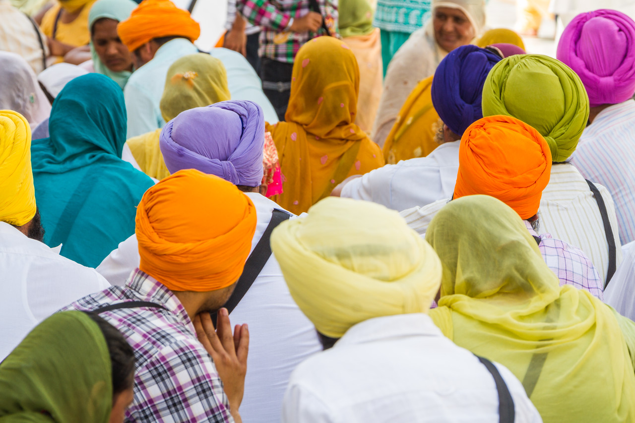 People wearing colourful turban praying in temple - India