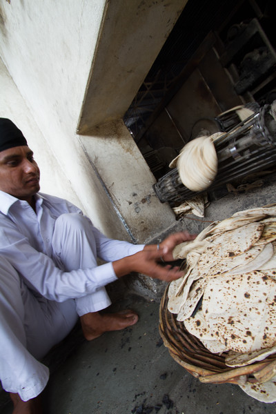 Chapatti coming out of oven in temple - India