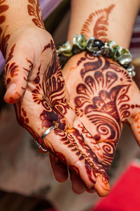 Woman shows henna tattoo on palm - India