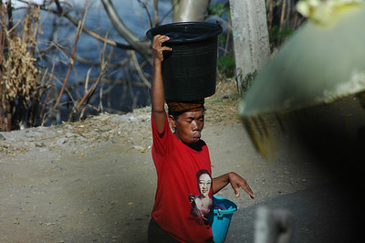 Carrying water from the sea, Bali, Indonesia.The T-shirt pictures Megawati Sukarnoputri, Indonesia's only female leader.