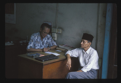 Office worker with abacus and adding machine, Bintan Island, Indonesia.