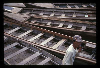 Boats and smoking man, Bintan Island, Indonesia.