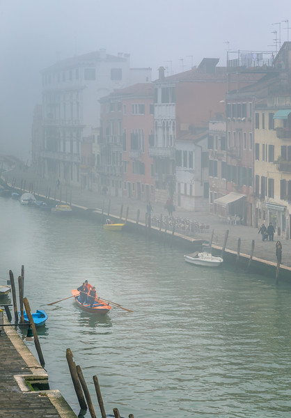 Group of people rowing gondola style in the early morning mist.