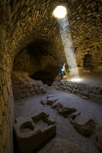 Light From A Hole In Karak Castle Fills An Old Kitchen As A Child Plays, Jordan