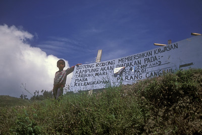 Boy with sign, rural Malaysia.