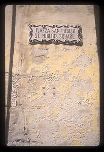 Sign and plaster, St. Publius Square, Malta.