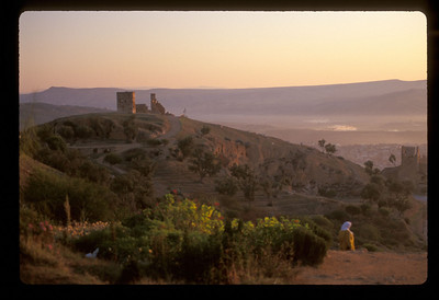 Woman and castle ruins at dawn, outside Fez, Morocco.