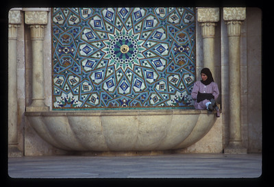 Woman on fountain outside Hassan II mosque, Casablanca, Morocco.