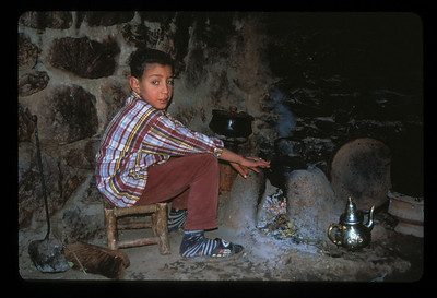 Boy with fire and teapot, village in Atlas Mountains, Fez, Morocco.