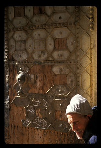 Man at door to mosque courtyard, old town Fez, Morocco.