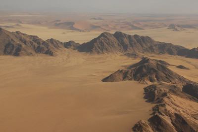 Aerial view of dunes and mountains near entrance to Namib-Naukluft Park, Namibia.