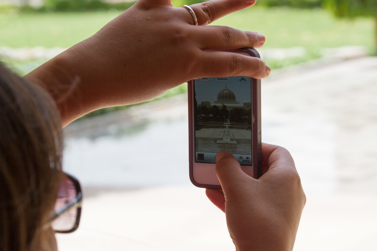 Woman taking picture of Sultan Qaboos Grand Mosque in mobile phone - Oman - Muscat