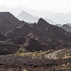 Landscape with single track and rocky mountains in background - Oman