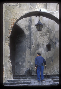 Man with cane on walkway, Sighisoara, Transylvania, Romania.