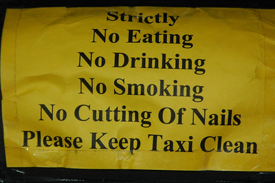 Notice on back seat of taxi, Singapore.