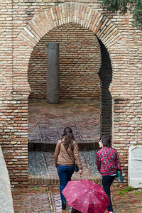 Tourist entering brick wall gate - Spain - Malaga