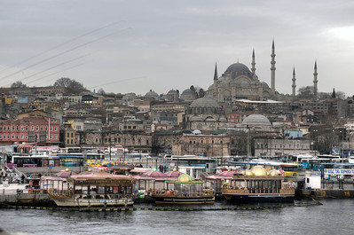 View Across the Golden Horn to Eminönü, Istanbul, Turkey. The Rüstem Pasha Mosque, background. This photo was taken on the Galata Bridge. Those are fishing rods against the sky on the left.