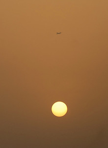 Airliner over the setting sun, Dubai, United Arab Emirates.