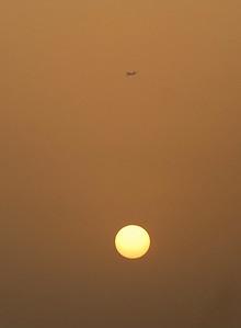 Airliner over the setting sun, Dubai, United Arab Emirates.