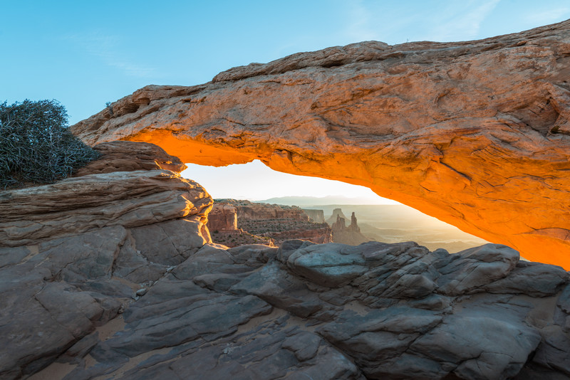 The glow of the rising sun reflects off the bottom of Mesa Arch in Canyonlands National Park in Utah.