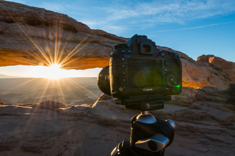 A Canon camera sits on a tripod to capture the rising sun underneath Mesa Arch in Canyonlands National Park, Utah.