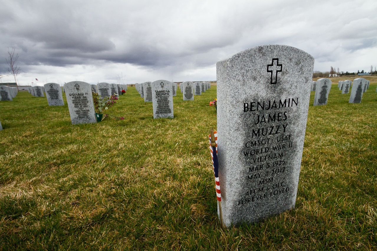 Miltary grave tombstones with American flags sit under a gray sky in Eastern Washington state, USA