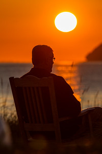 Man sitting on chair at sunset - USA - Washington - Bellingham