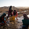 Internally displaced girls fill jerry cans with water to carry back to their settlement in Kamar Kulagh.<br /> <br /> Herat, May 2017<br /> <br /> Photo NRC/Jim Huylebroek