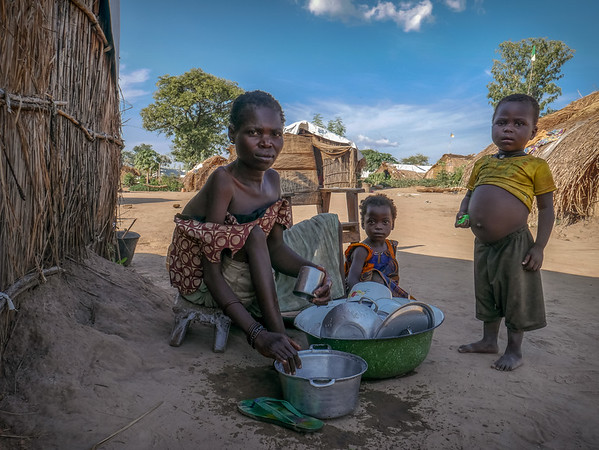 """In 2016, Philomene and her 6 children began a life in displacement after their village was targeted by armed men. After seeking refuge in a Catholic Church where they stayed for a year, she reached the camp of Lazare, Kaga Bandoro, in which they have been living for over a year. Philomene is disabled. She suffers from muscle dystrophy. Three years ago, her husband died of an untreated disease.<br /> <br /> """"I wish I could use my legs so my son would not need to skip school to fetch firewood. This our only source of income. He fetches the wood and I sell it. I earn about 300 Francs CFA (46 cents) a day, just enough to buy manioc powder.<br /> <br /> """"I should be the one taking care of my eldest but instead it is him who is taking of me. When armed men attacked our village, he took all my siblings and ran away. I am disabled so why would they want to kill me? However, I also fled because everyone left the village.<br /> <br /> """"I scrawled on my hands and feet and reached the bush. I stayed and hid in the bush for a week. I was terrified. There was no one around. There was no food but I was not even hungry because I was petrified. The most difficult was to not find water so I drunk stagnant water.<br /> <br /> """"I fell sick but luckily after a week I reached the church where many other families took refuge. I found my children there. We stayed there for a year.<br /> <br /> """"I am afraid to return home because we are alone. I am afraid that they come and attack us again.<br /> <br /> """"I am not at ease here either but it is better than being there alone. I have a lot of nightmares in which I see my children being attacked by owls and cats. I wake up every night to pray for these nightmares to stop.<br /> <br /> """"If you want to share my story, then I also want to ask for a wheelchair. I am tired of crawling. My body is sore.""""<br /> <br /> <br /> <br /> Credit: Hajer Naili/NRC"""