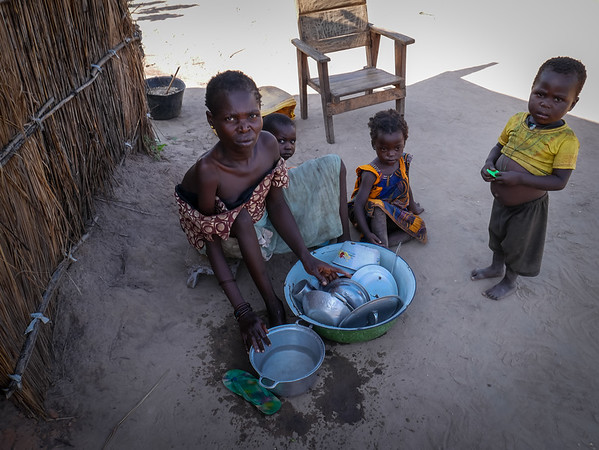 """In 2016, Philomene and her 6 children began a life in displacement after their village was targeted by armed men. After seeking refuge in a Catholic Church where they stayed for a year, she reached the camp of Lazare in which they have been living for over a year. Philomene is disabled. She suffers from muscle dystrophy. Three years ago, her husband died of an untreated disease.<br /> <br /> """"I wish I could use my legs so my son would not need to skip school to fetch firewood. This our only source of income. He fetches the wood and I sell it. I earn about 300 Francs CFA (46 cents) a day, just enough to buy manioc powder.<br /> <br /> """"I should be the one taking care of my eldest but instead it is him who is taking of me. When armed men attacked our village, he took all my siblings and ran away. I am disabled so why would they want to kill me? However, I also fled because everyone left the village.<br /> <br /> """"I scrawled on my hands and feet and reached the bush. I stayed and hid in the bush for a week. I was terrified. There was no one around. There was no food but I was not even hungry because I was petrified. The most difficult was to not find water so I drunk stagnant water.<br /> <br /> """"I fell sick but luckily after a week I reached the church where many other families took refuge. I found my children there. We stayed there for a year.<br /> <br /> """"I am afraid to return home because we are alone. I am afraid that they come and attack us again.<br /> <br /> """"I am not at ease here either but it is better than being there alone. I have a lot of nightmares in which I see my children being attacked by owls and cats. I wake up every night to pray for these nightmares to stop.<br /> <br /> """"If you want to share my story, then I also want to ask for a wheelchair. I am tired of crawling. My body is sore.""""<br /> <br /> <br /> <br /> Credit: Hajer Naili/NRC"""