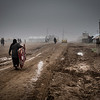 A displaced woman carrying a mattress in the muddy alleys of Hamam al Halil camp