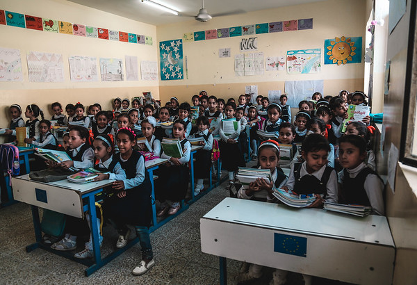 These are grade one students in Maimoona elementary school. Three to four students are sitting in one desk.