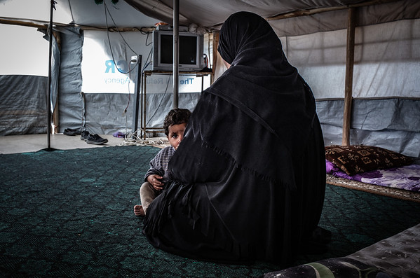 Hana and her undocumented son sitting in their tent - Displacement camp, Kirkuk