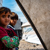 Two of Nada's undocumented daughters standing outside their tent in a displacement camp near Mosul