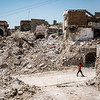 A man walks through the rubble of the old city of Mosul